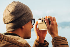 Hipster man takes photographs with vintage photo camera on coast Stock Photography