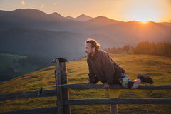 Hipster man travel in the mountains at sunset Stock Photos