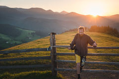 Hipster man travel in the mountains at sunset Stock Photo