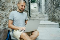 Hipster man and a traveler working on a laptop in the street.  Royalty Free Stock Photo