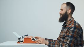 Hipster man typing with a red vintage typewriter. Side view of hipster man with red vintage typewriter sitting at table looking forward at blank copy space stock footage