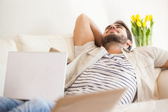 Hipster man using laptop lying on couch Royalty Free Stock Image