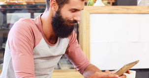 Hipster man using tablet. In cafe stock video footage