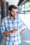 Hipster man using tablet computer in the city Royalty Free Stock Image
