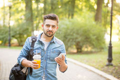 Hipster man walking along the road. Handsome hipster man walking along the road with smart phone and coktail. Serious man in jeans shirt posing with a black bag Stock Photo