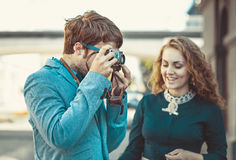 Hipster man wants to take a picture of a beautiful girl Royalty Free Stock Image