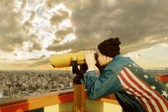 Hipster man wearing american flag jeans jacket looking through binocular lens against urban building royalty free stock photos