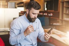 Hipster man working, checking email, blogging, reading, learning. Instagram filter. Young serious attractive bearded businessman in blue shirt sits on sofa in Stock Photos