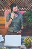 Hipster man working on laptop and using mobile phone while sitting on terrace of cafe. Attractive bearded man calling to. Friends.Vertical stock images