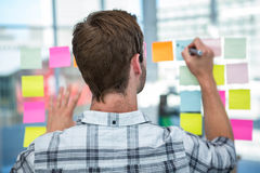 Hipster man writing on post-it Royalty Free Stock Photography