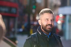 Hipster manager in black jacket walking in the street Royalty Free Stock Photos