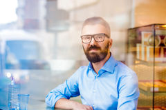 Hipster manager sitting in cafe by the window, reflection Royalty Free Stock Photo