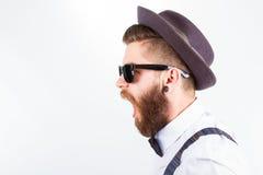 Hipster med hatten som gör roliga framsidor royaltyfria foton