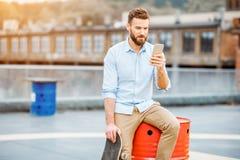 Hipster med smartphonen på taket arkivbild