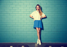 In Hipster-Meisje bij de Turkooise Bakstenen muur Stock Foto's