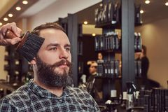 Professional hairdresser uses a brush, almost finished hairstyle. royalty free stock photos