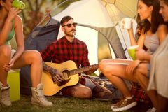 Hipster man camping with friends. Hipster men on camping playing guitar in the company of his friends stock photos