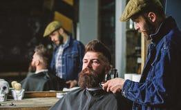 Hipster met baard die met kaap het in orde maken door professionele kapper in modieuze herenkapper wordt behandeld Kapper bezig m royalty-vrije stock afbeelding
