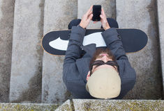 Hipster met skateboard en mobiel Stock Fotografie