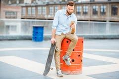 Hipster met smartphone op het dak stock afbeeldingen
