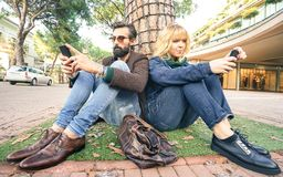 Hipster millennial couple in disinterest moment with smartphone - Apathy concept about sadness and isolation using mobile phone. Hipster millennial couple in stock images