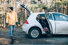 Couple next to small hybrid car in forest royalty free stock photos