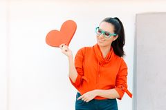 Young Girl Wearing Eyeglasses Holding Big Heart royalty free stock photo
