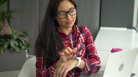 Hipster mixed race woman using smartwatch and working on laptop pc in cafe.  stock video footage
