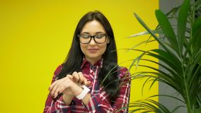 Hipster mixed race woman using smartwatch on yellow background.  stock footage