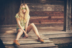 Hipster Model Girl Sitting on the Wooden Porch Royalty Free Stock Photo