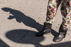 Hipster model legs wearing trousers with flowers, short black bo. Ots and shadow in the background Royalty Free Stock Photo