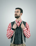 Hipster model looking away with raised eyebrow while holding his pants suspenders. Desaturated portrait of standing young hipster model looking away with raised Royalty Free Stock Image