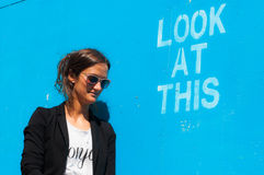 Hipster model wearing sunglasses posing next to Lo. Hipster model wearing sunglasses posing next to a blue wall with the words Look at this written on it Stock Image