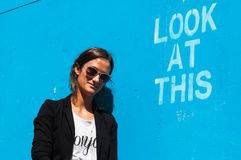 Hipster model wearing sunglasses posing next to Lo stock images