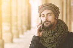 Hipster modern man using smart phone in urban contexr warm filte Stock Image