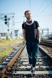 Hipster modern stylish blonde man on rails. In daily life Royalty Free Stock Images