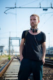 Hipster modern stylish blonde man on rails Royalty Free Stock Image