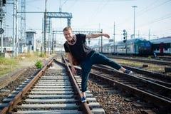 Hipster modern stylish blonde man on rails Stock Photos