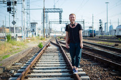 Hipster modern stylish blonde man on rails Royalty Free Stock Photos