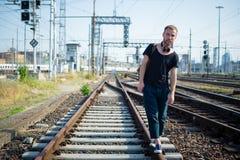 Hipster modern stylish blonde man on rails Stock Photography