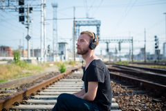 Hipster modern stylish blonde man on rails Stock Photo