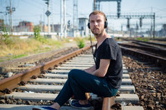 Hipster modern stylish blonde man on rails Stock Photos