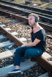 Hipster modern stylish blonde man on rails Royalty Free Stock Image