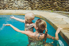 Hipster Mother play with her lovely child in swimming-pool, Bali. Ubud royalty free stock image