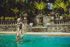 Hipster Mother play with her lovely child in swimming-pool, Bali. Ubud stock photos