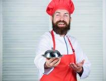 Εξυπηρετήστε τα τρόφιμα Κουζίνα μαγειρική το άτομο κρατά το δίσκο πιάτων κουζινών στο εστιατόριο Υγιές μαγείρεμα τροφίμων Ώριμο h στοκ φωτογραφίες με δικαίωμα ελεύθερης χρήσης