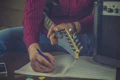 Hipster musician sits on the couch with an electric guitar and r royalty free stock photography