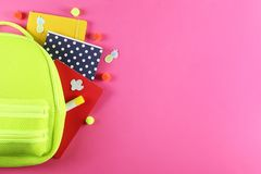 Set of school supplies on paper textured background. Hipster neon green textile backpack, surrounded with school supplies. Back to school concept. Lots of royalty free stock images