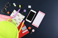 Set of school supplies on paper textured background. Hipster neon green textile backpack, surrounded with school supplies. Back to school concept. Lots of royalty free stock photography