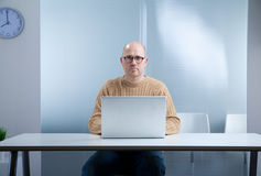 Hipster nerd bald with laptop. Office worker with a nerd attitude and an open laptop on the top of an empty desktop in an almost empty room waiting for you to stock photos